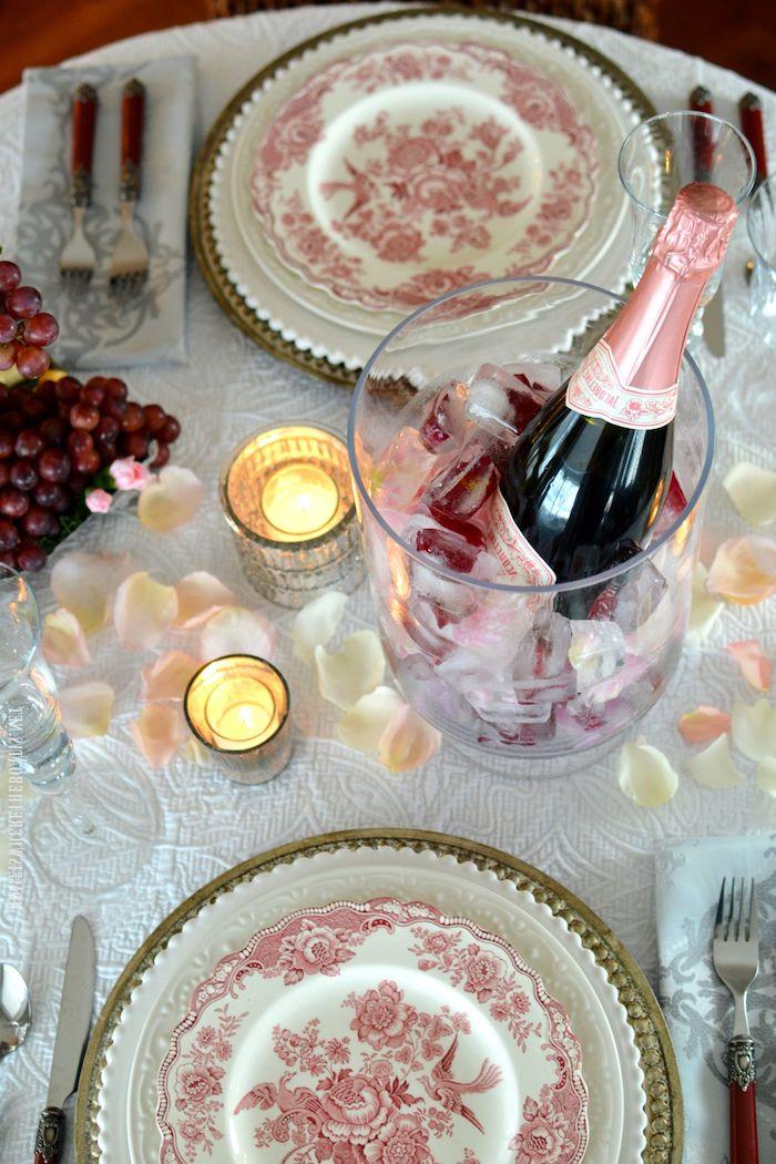 diner romantique avec deux assiettes en porcelaine un seau de champagne des bougies et petales de rose