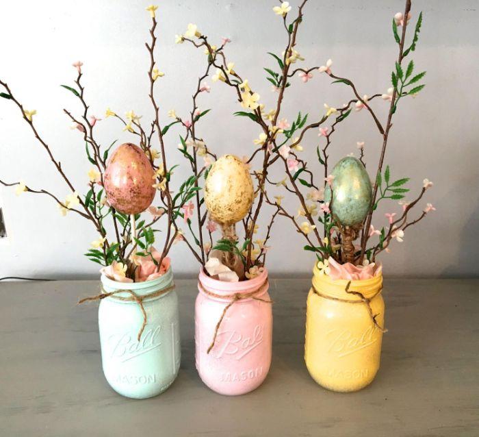 exemple activité manuelle paques pots repeints de peinture colorée avec des branches fleuries et des oeufs colorés dans papier