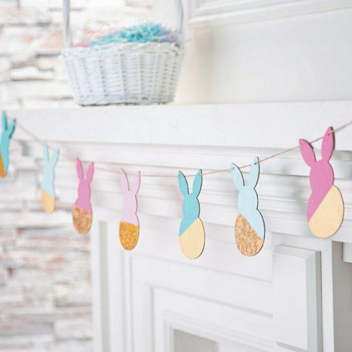 fabriquer une guirlande de paques en figurines de lapin en liège colorés de peinture pour décorer une cheminée