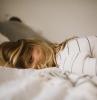 fille blonde sur un lit blouse aux rayures blanc noir