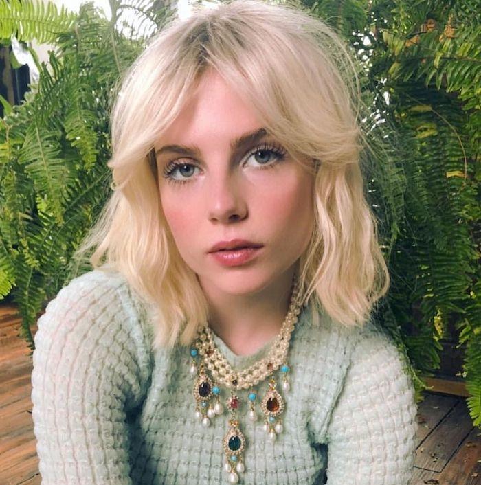 frange bardot une femme blonde devant plantes vertes vetue en blouse tricote portante des coliers