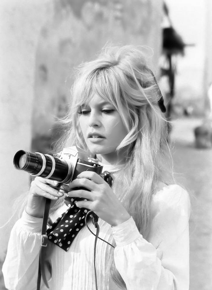frange brigitte bardot qui tient un apareil foto une image en noir et blanc