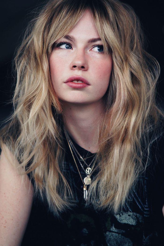 frange cheveux long une femme blonde qui porte un colier vetue en top noir