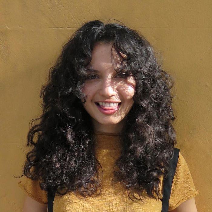 frange légère pour une coiffure boucle une femme avec blouse jaune et des bretelles