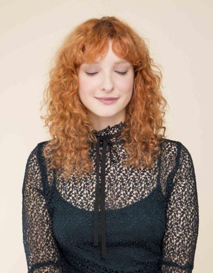 frange rideau dégradé sur une femme aux cheveux rouges et bouclés vetue en top en dentelle noire