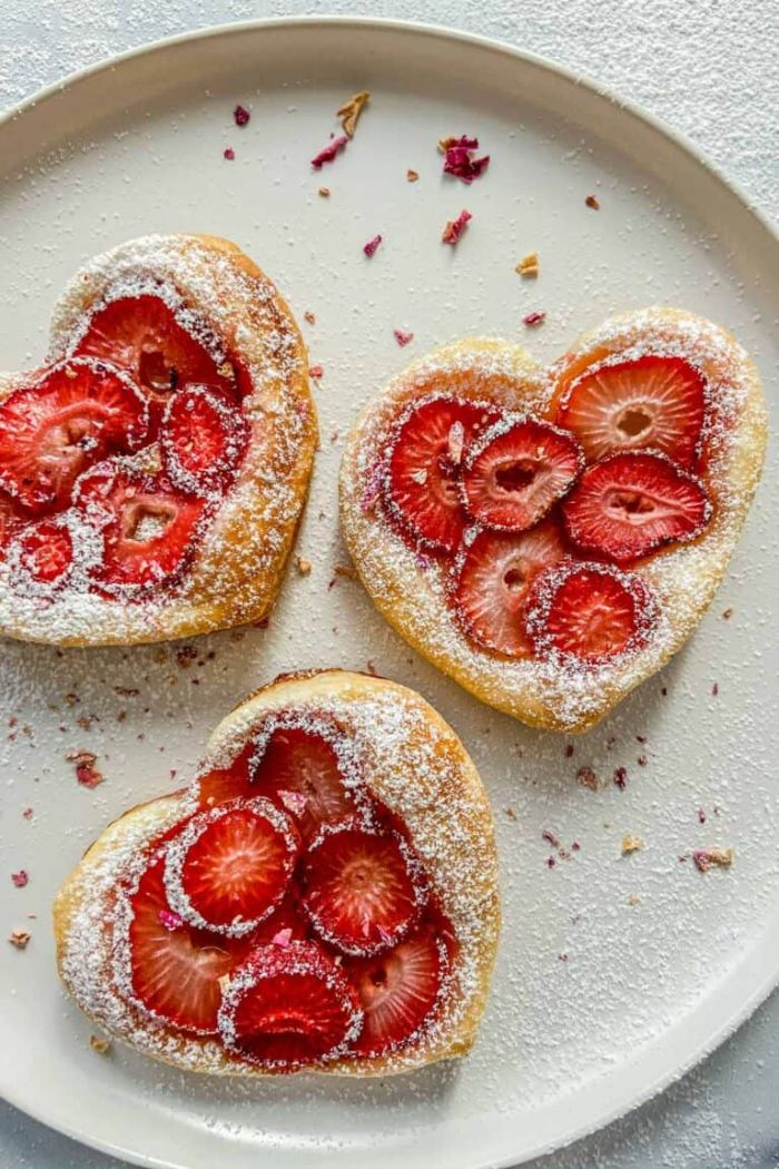 gâteau à la fraise en forme de coeur tartalette pâte feuilletée fraises et sucre glace dans assiette