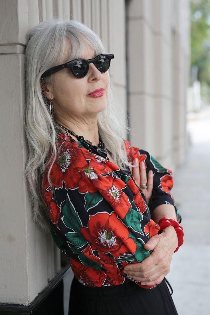 garde robe idéale femme 60 ans avec chemise à fleurs rouges sur fond noir et jupe longue noire