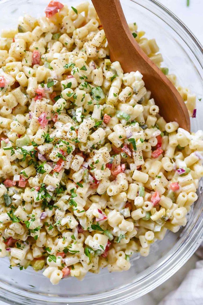 garniture wrap sous forme de salade de pates legumes et mayonnaise avec un cuillère en bois