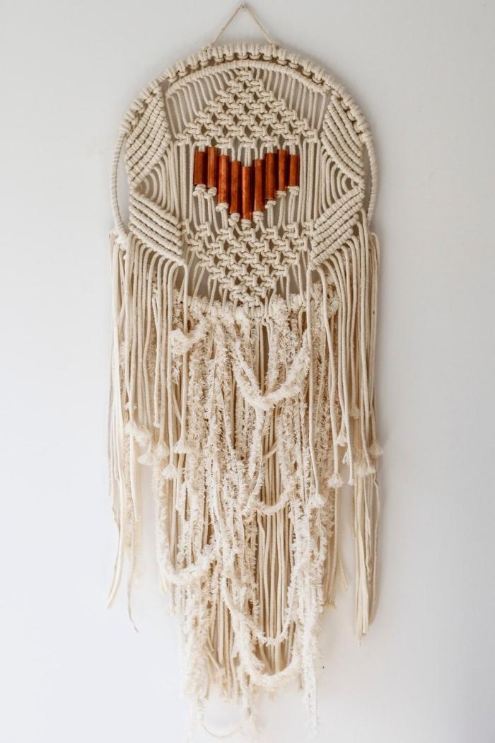 grand attrape reve avec coeur forme au centre embellissement métal noeud macramé cercle bois