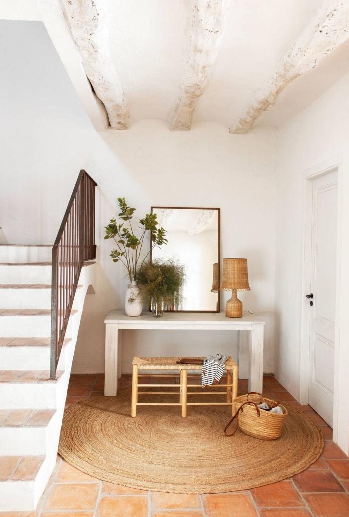 hall d entrée tapis rond jute miroir escalier blanc et bois lampe fibre végétale vase blanc