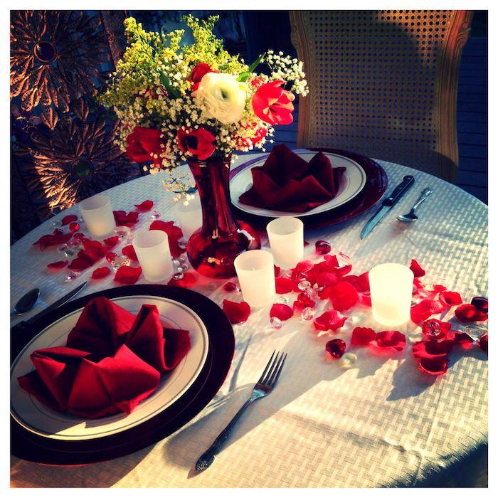 idée repas amoureux avec deux serviettes rouges dans des assietes chemin de table en petales et chandelles