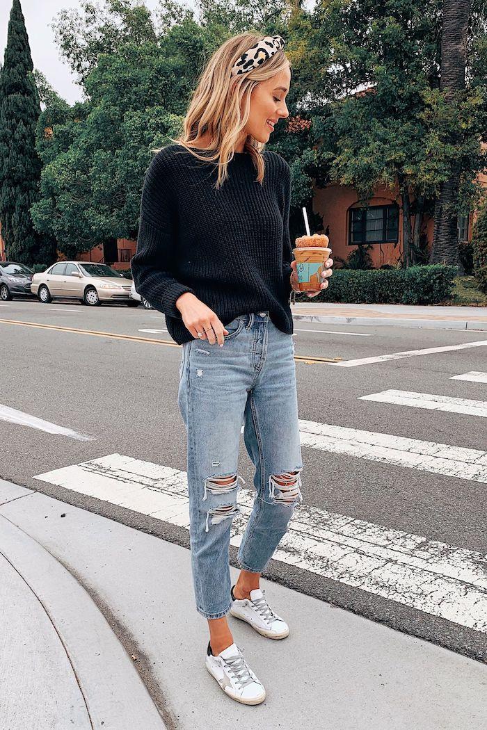 jean mom déchiré combiné avec une blouse tricoté et des baskets blanches une fille qui tient café froid