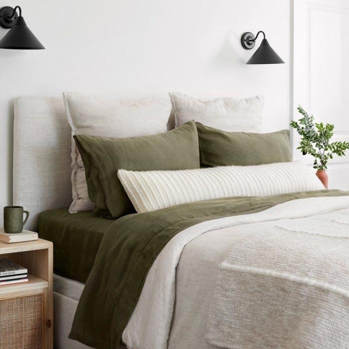 linge de lit déco de chambre kaki accents taie oreillers couverture vert foncé tasse de café meuble chevet bois rotin