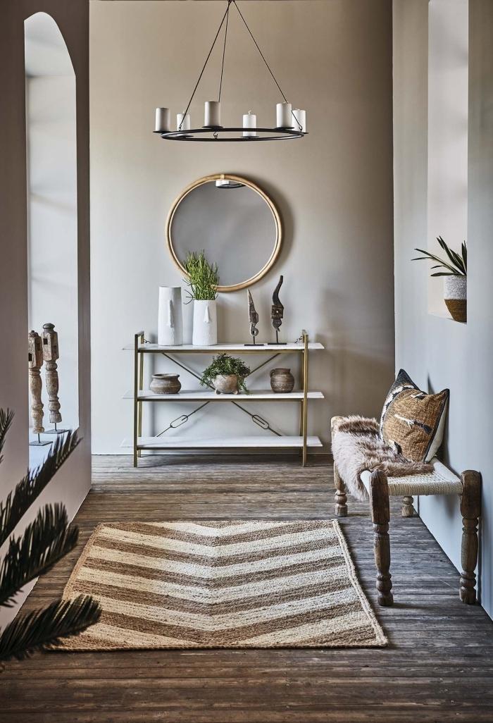meubles bois et or banquette bois tapis beige et blanc plante verte peinture couloir étroit miroir rond