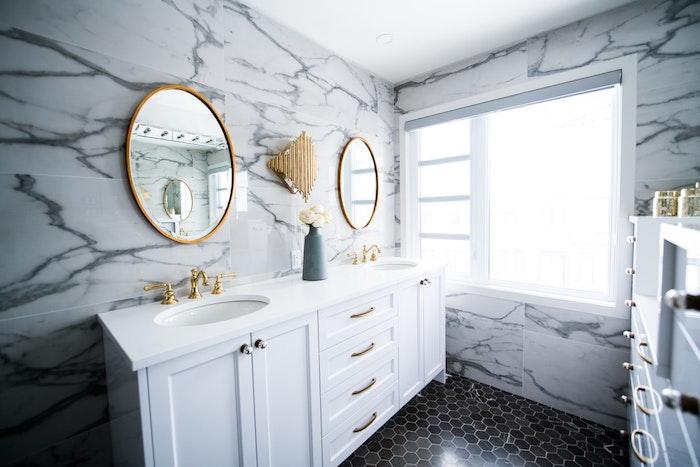 miroir rond accroché au mur salle de bain avec encadrement laiton idee deco salle de bain marbre et laiton elegante