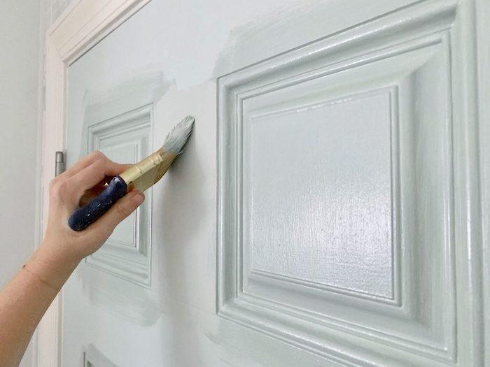 peindre une porte a l aide d un pinceau et de la peinture blanche