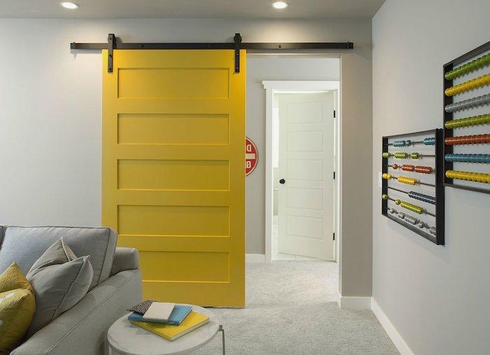 peindre une porte intérieure glissante en couleur jaune lumineux dans la salle de sejour aveec des coussins jaune et cananpé gris