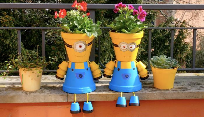 personnage en pot de fleur des miniions décoratives assises au bord d un jardin a coté des deux fleurs.jpg