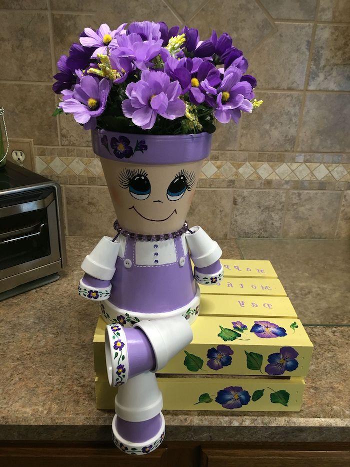 personnage en pot de fleur posé sur le comptir dans la cuisine et peint en couleurs violets