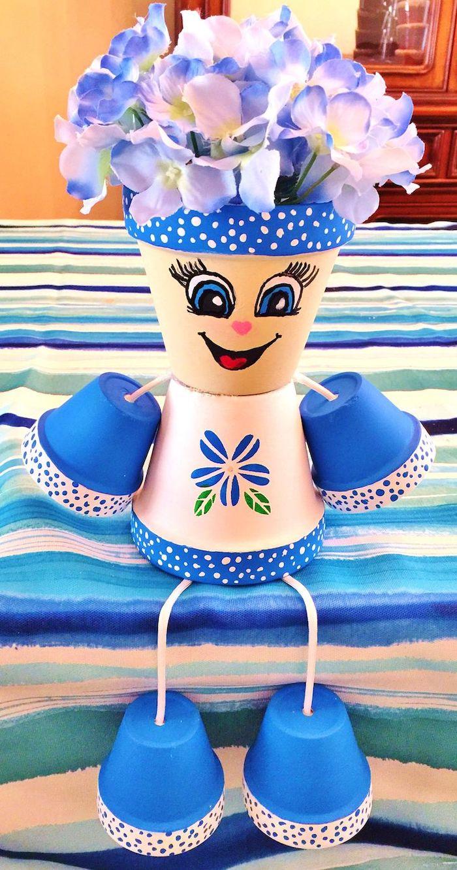 personnage ne pot de fleur une idéee de décoration en couleur bleu et blanc avec des fleures fausses sur la tete