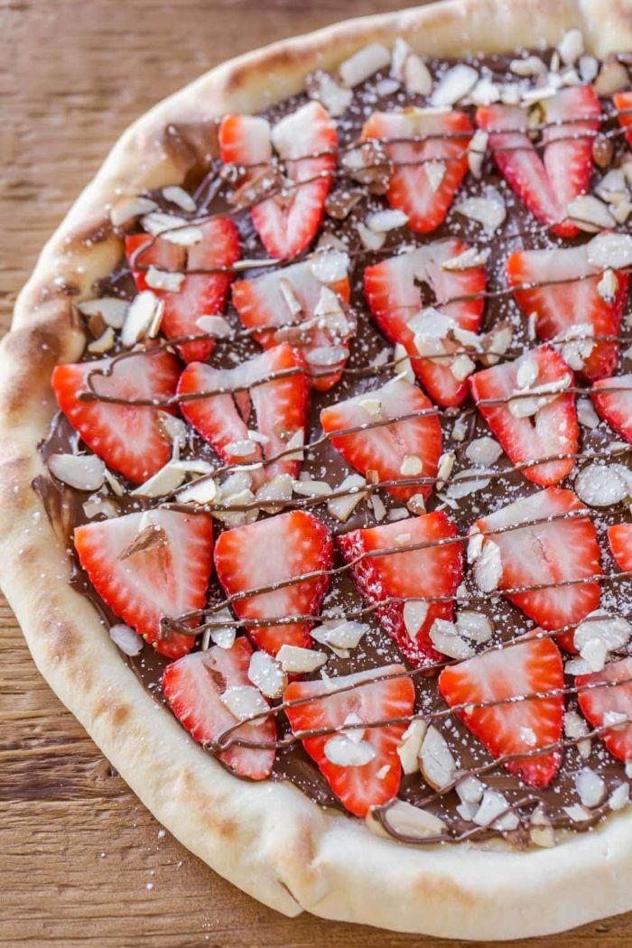 pizza maison sucrée à base de nutella et fraise avec des amandes hachés faire un dessert original au chocolat