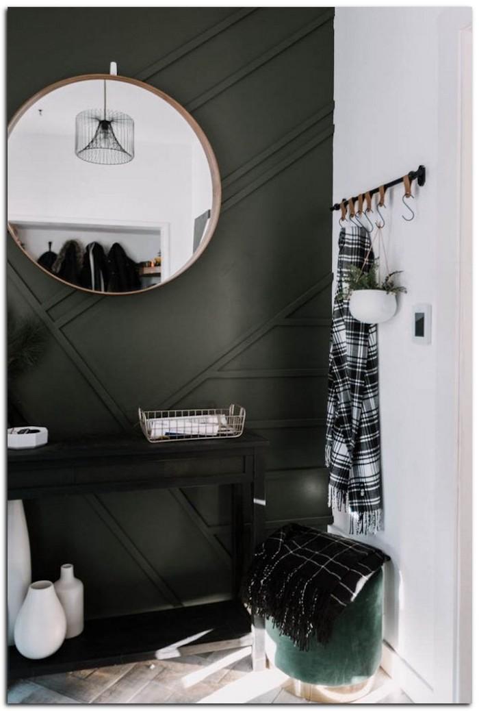 plante a suspendre accroché dans une entrée avec un miroir ronde et une tabourette en velours vert