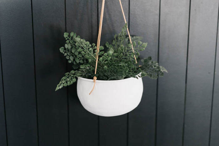 pot de fleur à suspendre contre un mur noir un conteneur peint en blanc et accroché a l aide d une corde en cuir