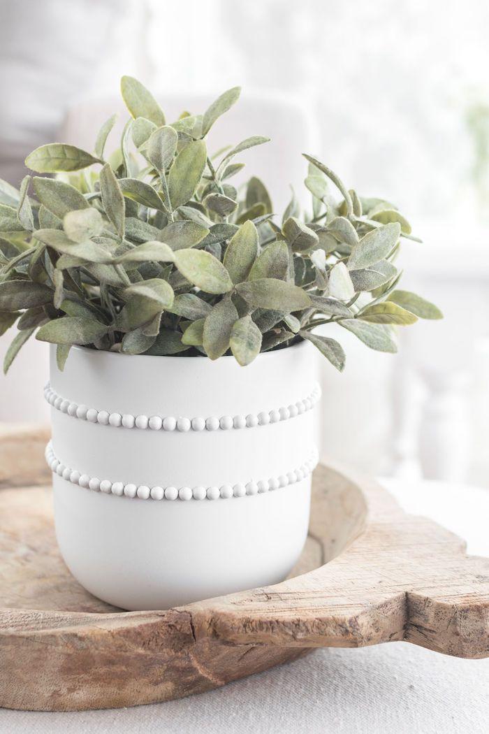 pot de fleur original en)blanche avec deux rangés des perles fausses posé sur un plateau rustique en bois