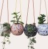pot de fleur suspendu et accrochée avec des cordes colores déssinées a motifs abstraits