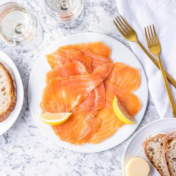 présentation saumon fumé avec du ctiron dans une assiette en porcelaine et des tranches de pain