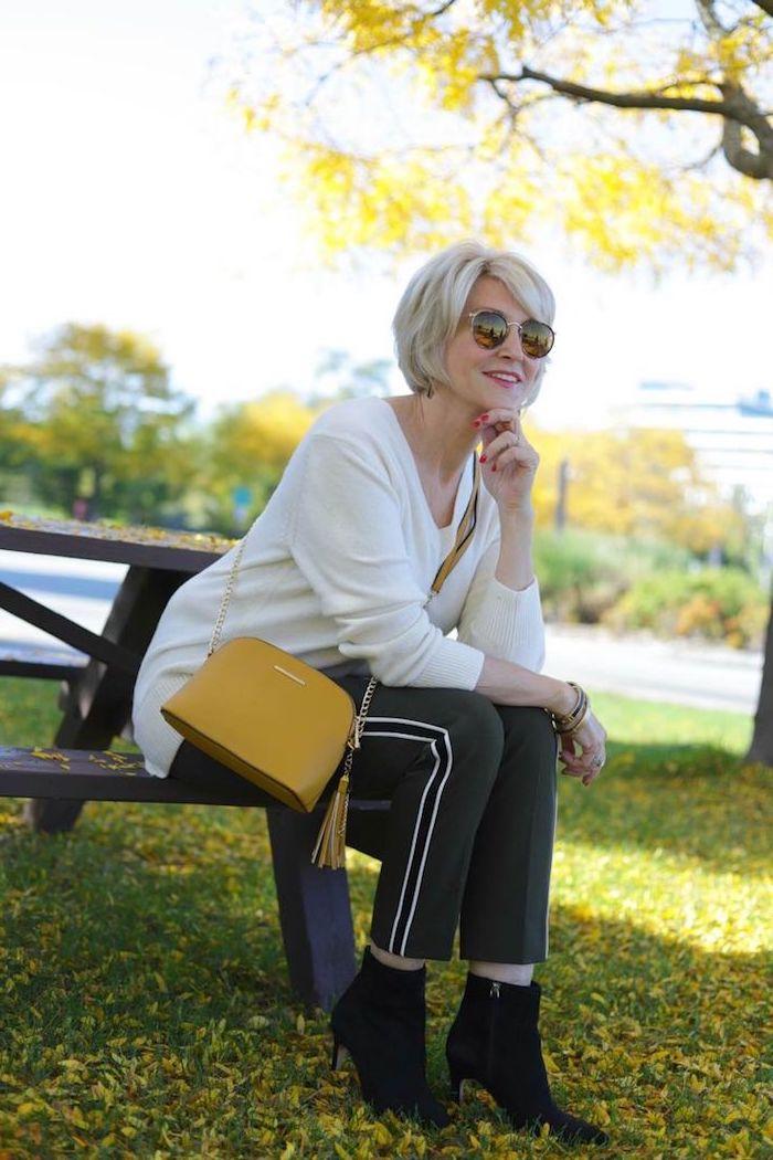 pull femme blanc pantalon noir à rayures blanches sac à main jaune femme assise sur banc manucure rouge