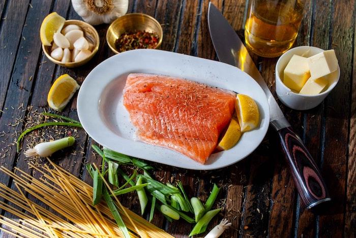 que manger avec des tranches de saumon fumé un filet sur la table avec de l ail des cubes de beurre et de poivre
