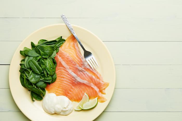 recette a base de saumon fumé dans une assiette avec des épinards mayonnaise et de citron