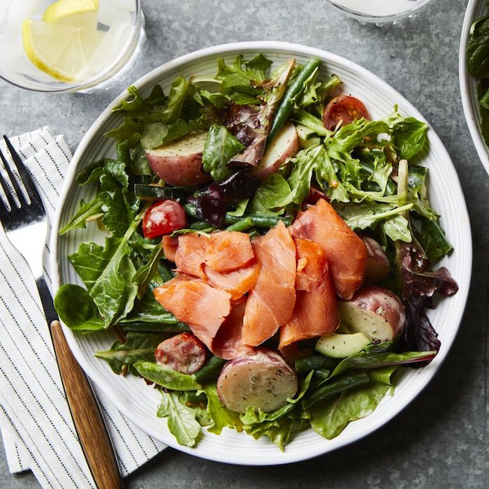 recette avec du saumon fumé avec de la salade verte des pommes de terre dans une assiette servie avec une verre d eau au citron