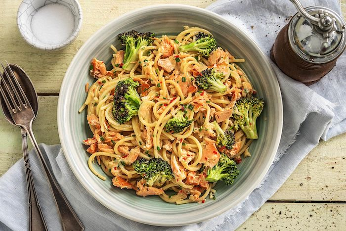 recette avec du saumon fumé en tranches des pâtes ax broccolis et poisson sur une nappe a coté des couverts