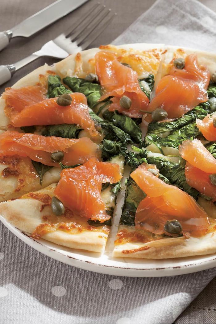 recette avec saumon fumé en tranches sur un pizza garnie des epinards et des capres