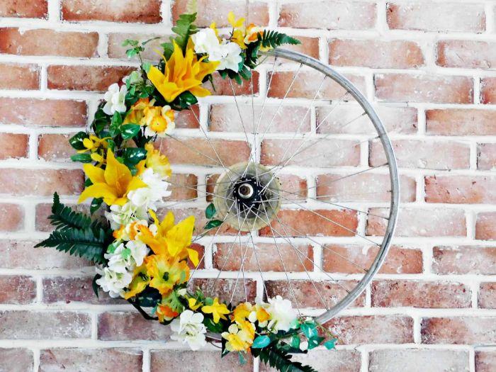 recyclage de roue décoréde fleurs artificielles jaunes et blanches decoration murale exterieur a fabriquer soi meme