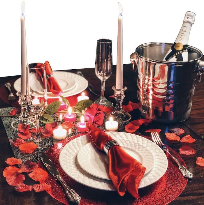 repas romantique une idée de mettre la table avec des pétales de rose et des bousies des serviettes rouges dans deux assiettes