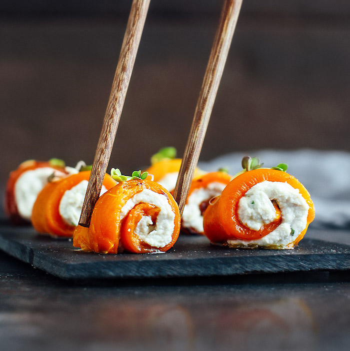 roulé saumon fumé avec fromage frais servi sur un plateau noir avrc des baguettes recette asiatique