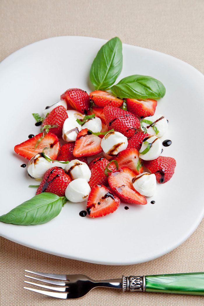 salade de fraises aux boules de mozzarella basilic et du basilic frais haché dans assiette blanche