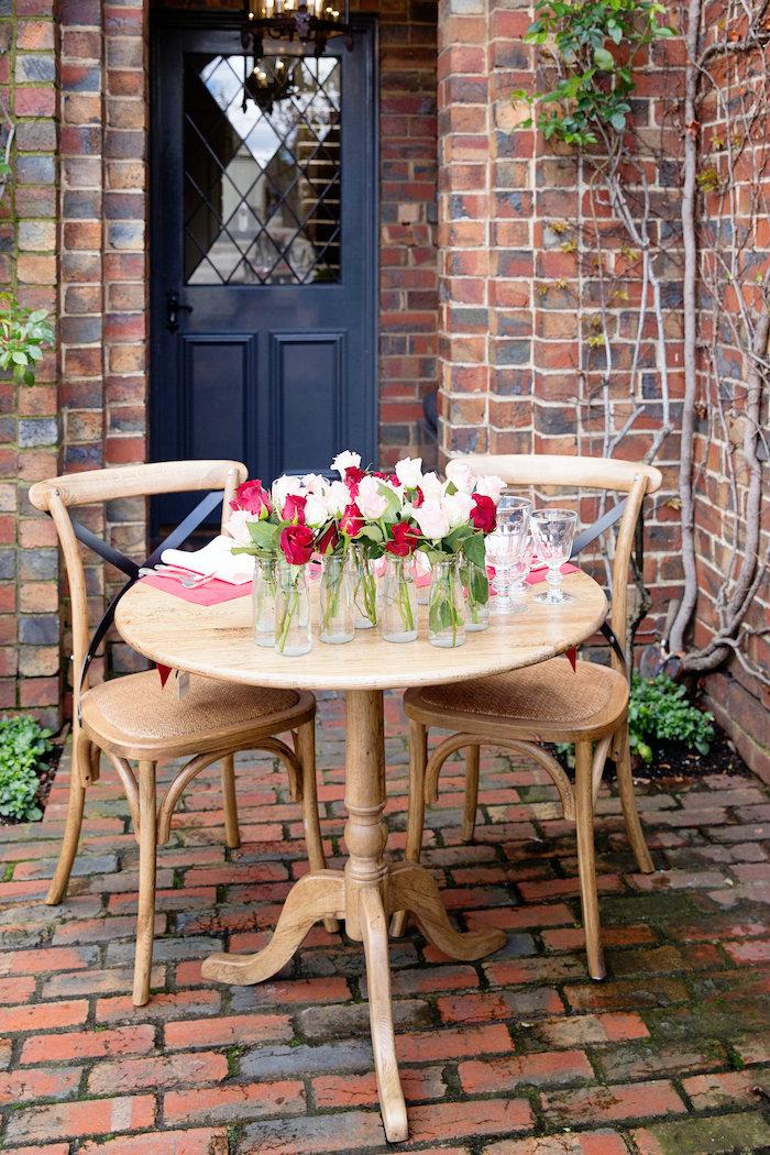 table romantique en dehors pour la fete de saint valentin décoré des nombreuses vases aux roses