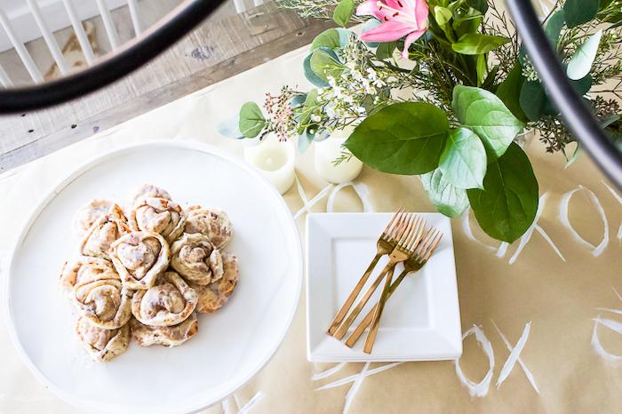 table romantique pour saint valentin avec une nappe en papier et des rouleaux a la canelle dans une assiette