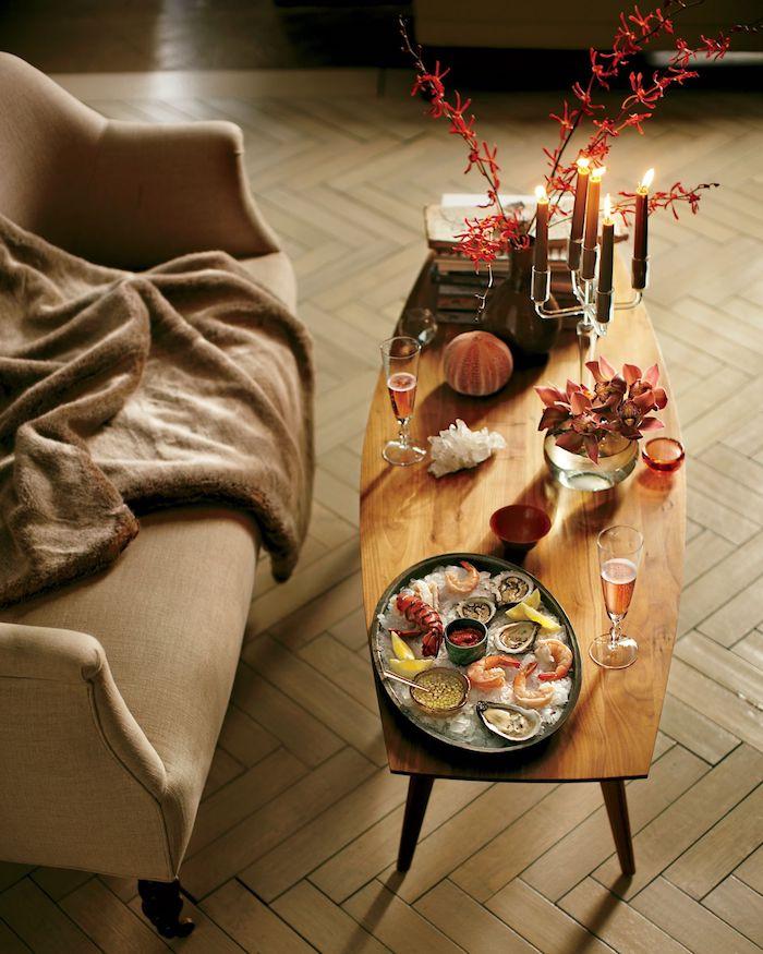 table saint valentin avec des fruits de mer deux verres rose devant le canape beige