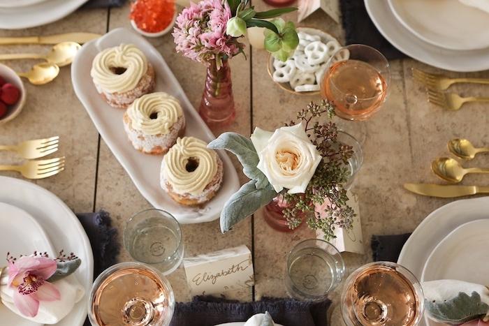 table saint valentin avec des patisseries et des verres remplies de vin rose et couvert dorees