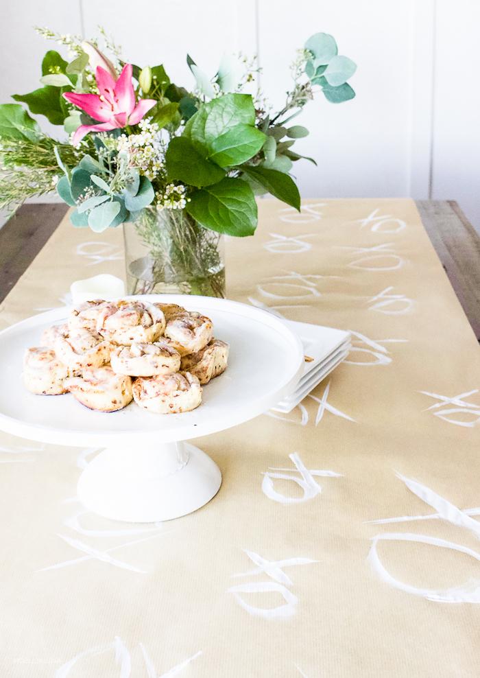 table saint valentin avec une nappe en papier dessinée et un bouquet de verdure