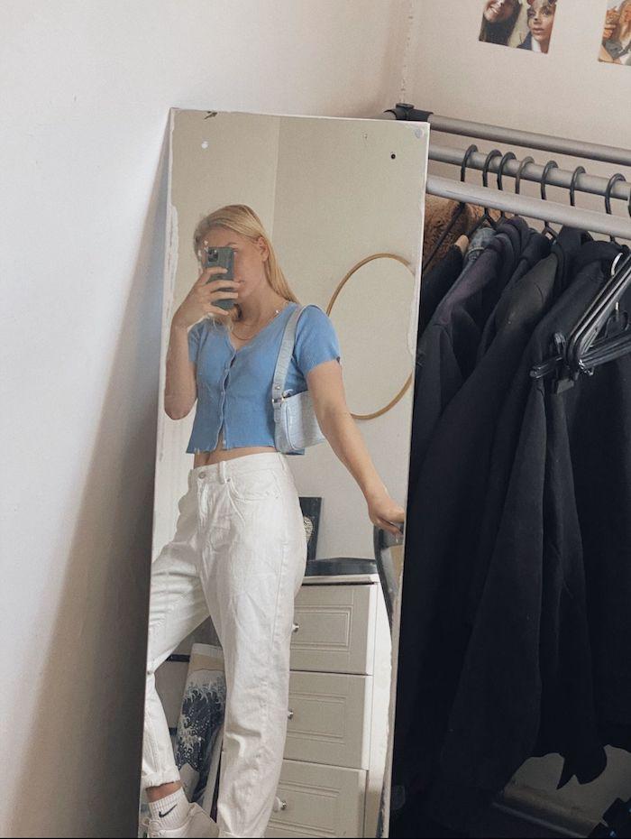 tenue avec jean mom blanc une femme qui se prend une photo dans le miroir vetue en top bleu