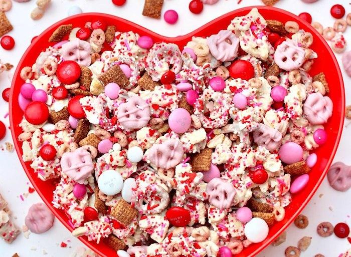 un bol en forme de coeur rempli des bonbons et des gourmandies pour saint valentin