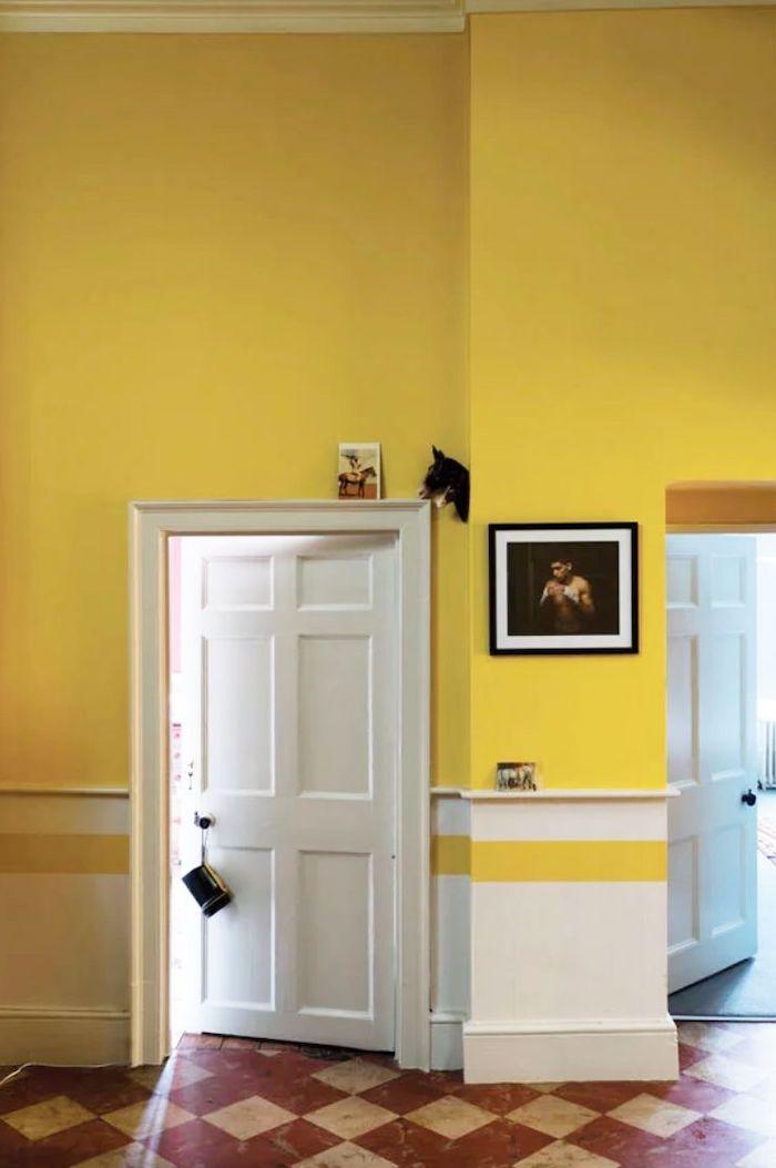 un couloiur peint en deux couleurs blanc et jaune lumineux avec des carreaux bruns au sol t une porte en bois
