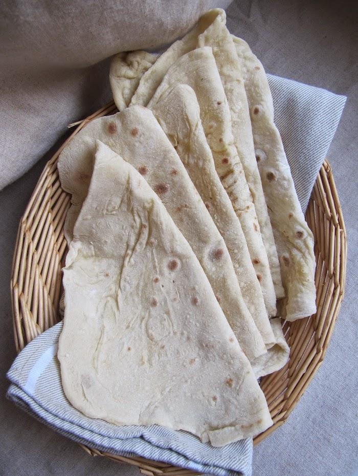 un pain lavash dans un panier en paille sur une nappe recette galette tacos