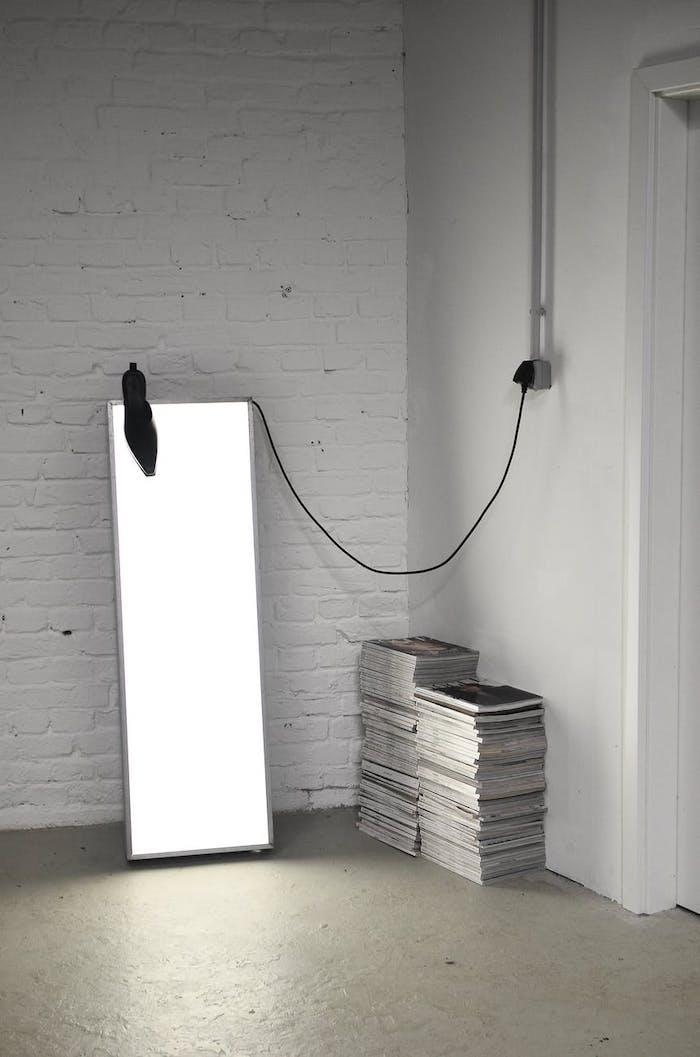 un panneau led devant mur des tuiles a coté d un pile des magazines